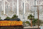 A freight train shuffles past a windmill farm, Palm Springs.