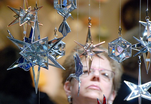 Craft show attendee pondering dangling glass forms.