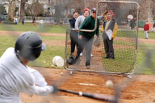 Young batter swings, as watchful eyes look on