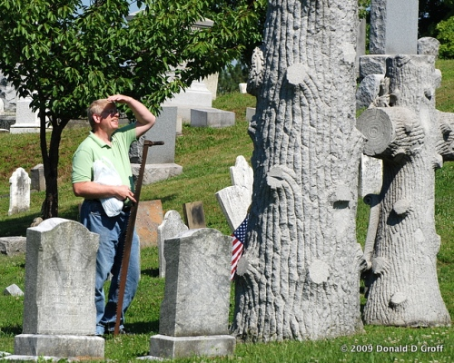 Man with cross-cut saw sizes up a tree-motif headstone, Somerset, PA