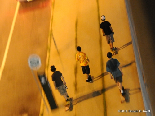 On a steamy July night, skateboarders move west along Callowhill street.
