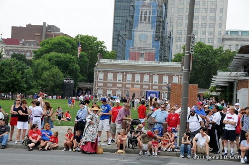celebrants gather to await the parade while ceremony unfolds at Independence Hall in background.